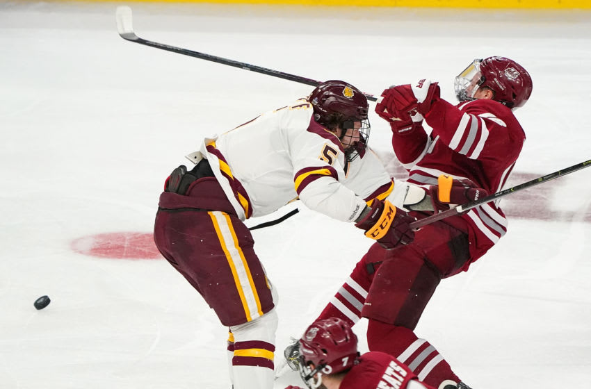 BUFFALO, NY - APRIL 13: Nick Wolff #5 of the Minnesota-Duluth Bulldogs checks Cale Makar #16 of the Massachusetts Minutemen during the second period at KeyBank Center on April 13, 2019 in Buffalo, New York. (Photo by Kevin Hoffman/Getty Images)