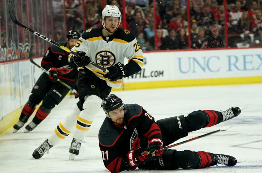 RALEIGH, NC - MAY 16: Nino Niederreiter #21 of the Carolina Hurricanes gets upended and attempts to control the puck on the ice as Brandon Carlo #25 of the Boston Bruins defends in Game Four of the Eastern Conference Third Round during the 2019 NHL Stanley Cup Playoffs on May 16, 2019 at PNC Arena in Raleigh, North Carolina. (Photo by Gregg Forwerck/NHLI via Getty Images)