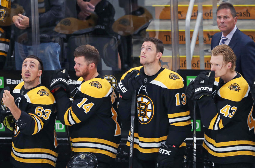 BOSTON - SEPTEMBER 23: From left, Boston Bruins players Brad Marchand (63), Chris Wagner (14), Charlie Coyle (13), Danton Heinen (43) and head coach Bruce Cassidy stand on the Boston bench during the singing of the national anthem. The Boston Bruins host the Philadelphia Flyers in a pre-season NHL hockey game at TD Garden in Boston on Sep. 23, 2019. (Photo by Jim Davis/The Boston Globe via Getty Images)