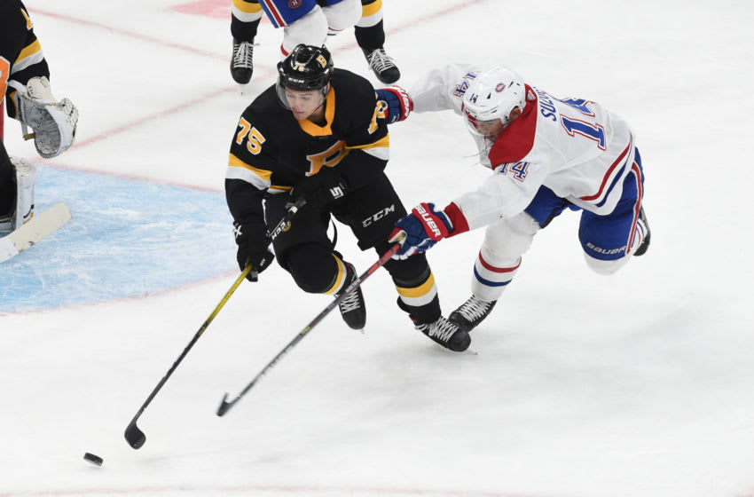 BOSTON, MA - DECEMBER 1: Connor Clifton #75 of the Boston Bruins skates with the puck against Nick Suzuki #14 of the Montreal Canadiens at the TD Garden on December 1, 2019 in Boston, Massachusetts. (Photo by Steve Babineau/NHLI via Getty Images)