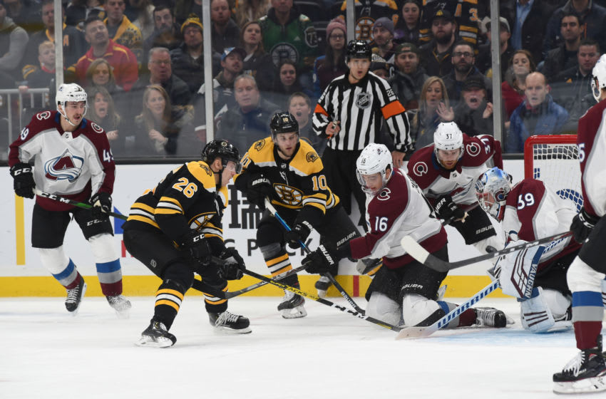 BOSTON, MA - DECEMBER 7: Nikkita Zadorov #16 of the Colorado Avalanche fights for the puck against Par Lindholm #26 and Anders Bjork #10 of the Boston Bruins at the TD Garden on December 7, 2019 in Boston, Massachusetts. (Photo by Steve Babineau/NHLI via Getty Images)