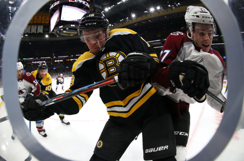 BOSTON, MASSACHUSETTS - DECEMBER 07: Brett Ritchie #18 of the Boston Bruins and Ryan Graves #27 of the Colorado Avalanche battle for the puck against the boards during the first period at TD Garden on December 07, 2019 in Boston, Massachusetts. (Photo by Maddie Meyer/Getty Images)