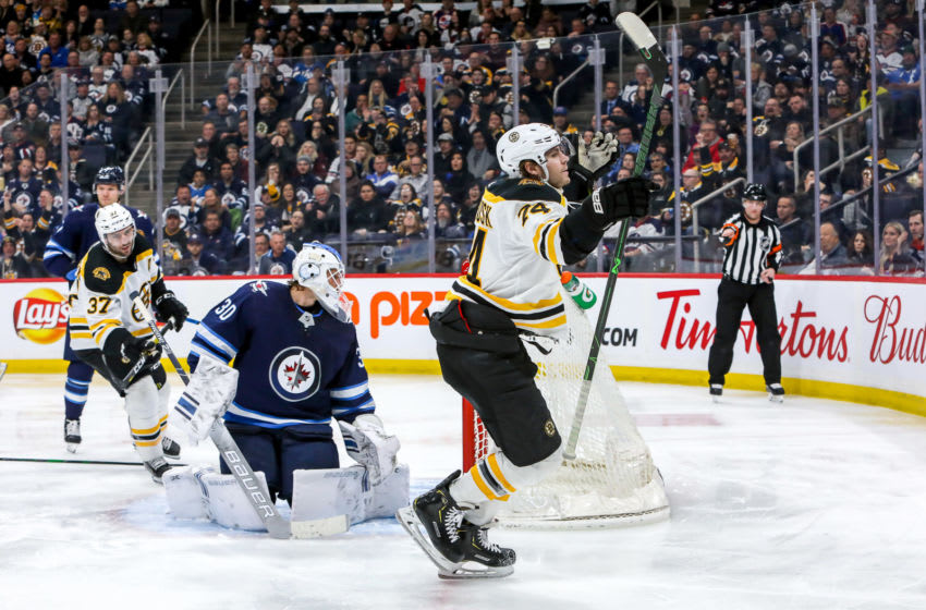 WINNIPEG, MB - JANUARY 31: Jake DeBrusk #74 of the Boston Bruins celebrates after scoring a third period goal against goaltender Laurent Brossoit #30 of the Winnipeg Jets at the Bell MTS Place on January 31, 2020 in Winnipeg, Manitoba, Canada. (Photo by Jonathan Kozub/NHLI via Getty Images)