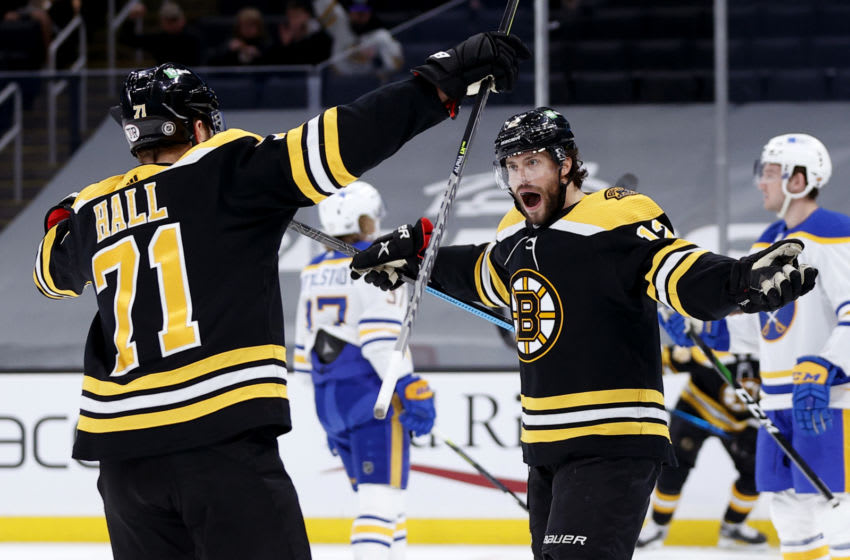 BOSTON, MASSACHUSETTS - MAY 01: Craig Smith #12 of the Boston Bruins celebrates with Taylor Hall #71 after scoring a goal against the Buffalo Sabres during the first period at TD Garden on May 01, 2021 in Boston, Massachusetts. (Photo by Maddie Meyer/Getty Images)