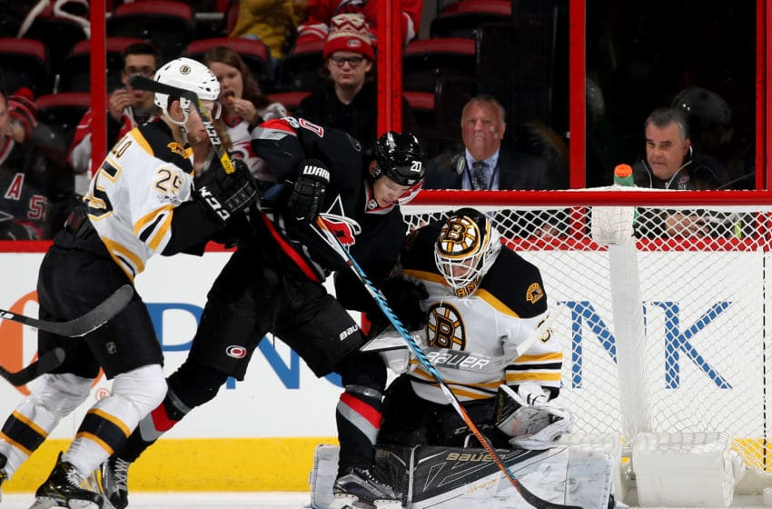 RALEIGH, NC - JANUARY 08: Sebastian Aho #20 of the Carolina Hurricanes looks to jam the puck in the net as Zane McIntrye #31 of the Boston Bruins goes down in the crease and Brandon Carlo #25 defends during an NHL game on January 8, 2017 at PNC Arena in Raleigh, North Carolina. (Photo by Gregg Forwerck/NHLI via Getty Images)
