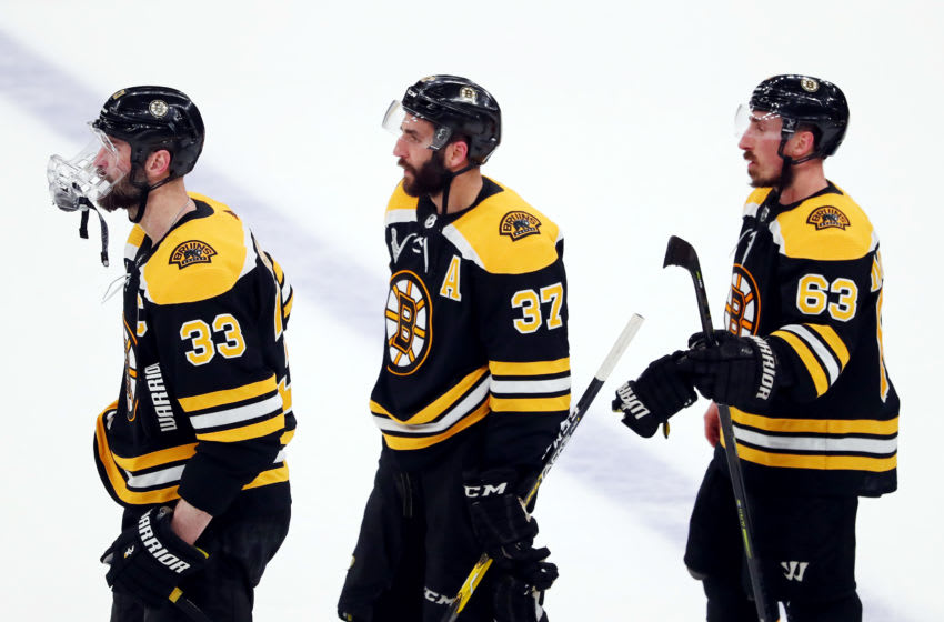 BOSTON, MASSACHUSETTS - JUNE 12: Zdeno Chara #33, Patrice Bergeron #37 and Brad Marchand #63 of the Boston Bruins await to shake the hands of the St. Louis Blues after losing Game Seven of the 2019 NHL Stanley Cup Final at TD Garden on June 12, 2019 in Boston, Massachusetts. (Photo by Adam Glanzman/Getty Images)