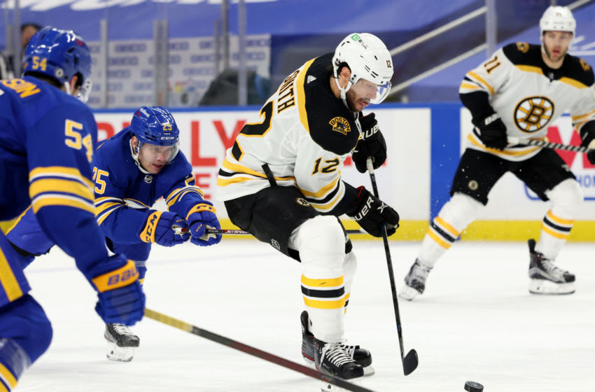 Apr 20, 2021; Buffalo, New York, USA; Buffalo Sabres center Arttu Ruotsalainen (25) tries to get the puck from Boston Bruins right wing Craig Smith (12) as he skates during the third period at KeyBank Center. Mandatory Credit: Timothy T. Ludwig-USA TODAY Sports