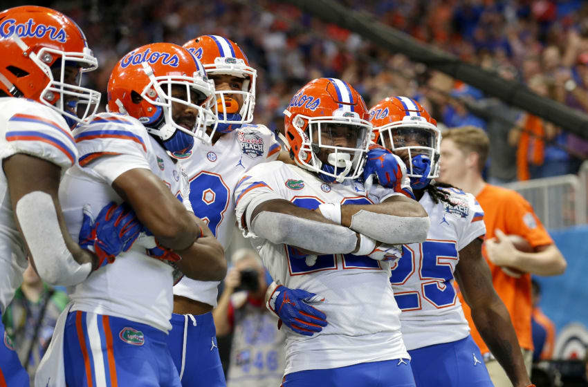 ATLANTA, GEORGIA - DECEMBER 29: Lamical Perine #22 of the Florida Gators is congratulated by his teammates after scoring a fourth quarter rushing touchdown against the Michigan Wolverines during the Chick-fil-A Peach Bowl at Mercedes-Benz Stadium on December 29, 2018 in Atlanta, Georgia. (Photo by Mike Zarrilli/Getty Images)
