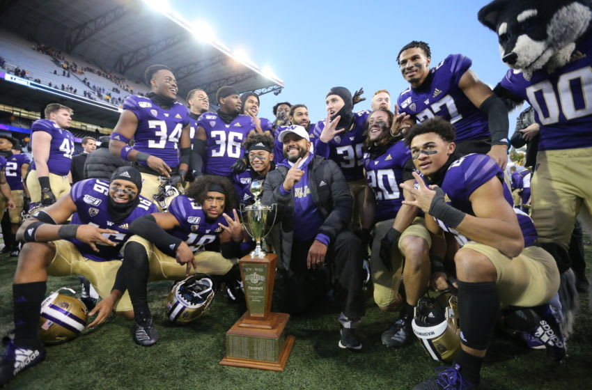 SEATTLE, WASHINGTON - NOVEMBER 29: The Washington Huskies pose with the Apple Cup trophy after defeating the Washington State Cougars 31-13 during their game at Husky Stadium on November 29, 2019 in Seattle, Washington. (Photo by Abbie Parr/Getty Images)