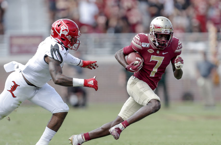 TALLAHASSEE, FL - SEPTEMBER 21: Wide Receiver D.J. Matthews #7 of the Florida State Seminoles avoids a tackle by Linebacker C.J. Avery #9 of the Louisville Cardinals during the game at Doak Campbell Stadium on Bobby Bowden Field on September 21, 2019 in Tallahassee, Florida. The Seminoles defeated the Cardinals 35 to 24. (Photo by Don Juan Moore/Getty Images)