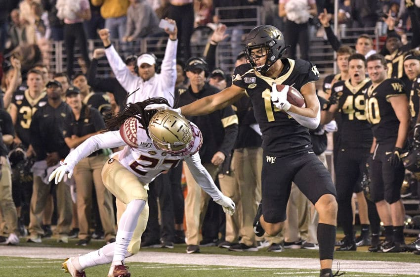 WINSTON SALEM, NORTH CAROLINA - OCTOBER 19: Sage Surratt #14 of the Wake Forest Demon Deacons makes a catch against Akeem Dent #27 of the Florida State Seminoles during the first half of their game at BB&T Field on October 19, 2019 in Winston Salem, North Carolina. (Photo by Grant Halverson/Getty Images)