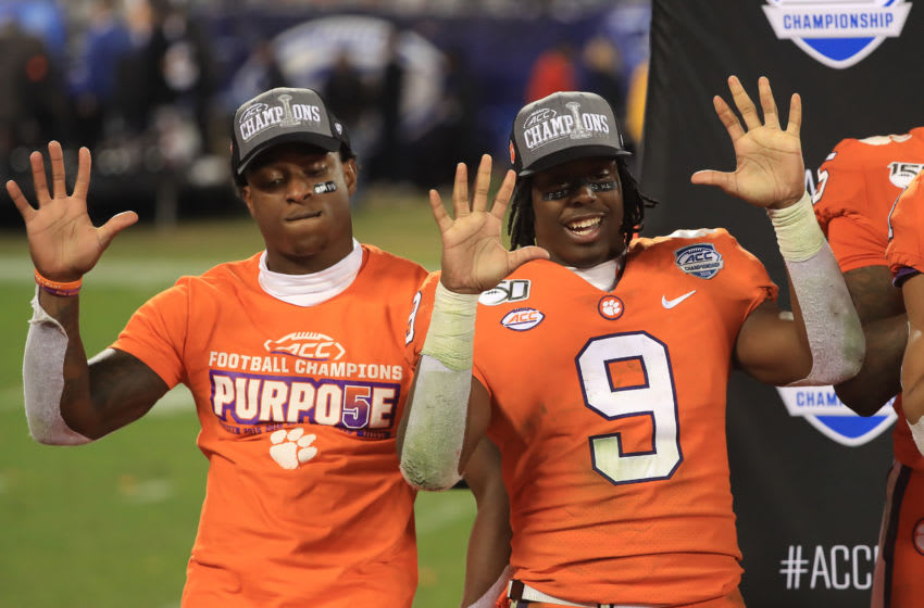 CHARLOTTE, NORTH CAROLINA - DECEMBER 07: Teammates K'Von Wallace #12 and Travis Etienne #9 of the Clemson Tigers celebrate after defeating the Virginia Cavaliers 64-17 in the ACC Football Championship game at Bank of America Stadium on December 07, 2019 in Charlotte, North Carolina. (Photo by Streeter Lecka/Getty Images)