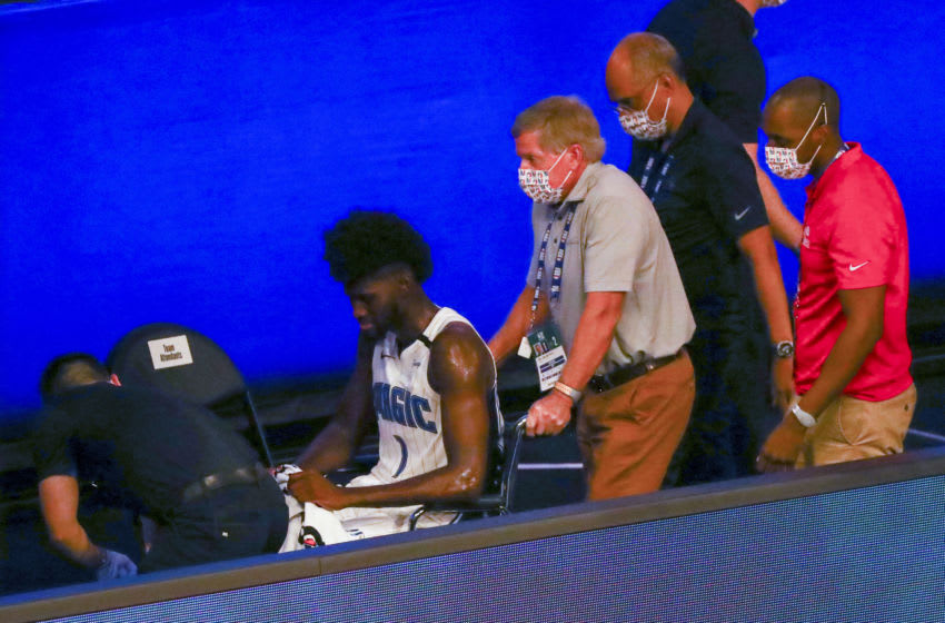 LAKE BUENA VISTA, FLORIDA - AUGUST 02: Jonathan Isaac #1 of the Orlando Magic is helped off the court in a wheelchair after an injury against the Sacramento Kings in the second half of a NBA basketball game at HP Field House at ESPN Wide World Of Sports Complex on August 2, 2020 in Lake Buena Vista, Florida. NOTE TO USER: User expressly acknowledges and agrees that, by downloading and or using this photograph, User is consenting to the terms and conditions of the Getty Images License Agreement. (Photo by Kim Klement-Pool/Getty Images)