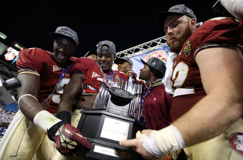 CHARLOTTE, NC - DECEMBER 01: Teammates Karlos Williams #9 of the Florida State Seminoles and James Wilder Jr. #32 celebrate with the trophy after defeating the Georgia Tech Yellow Jackets 21-15 in the 2012 ACC Championship game at Bank of America Stadium on December 1, 2012 in Charlotte, North Carolina. (Photo by Streeter Lecka/Getty Images)