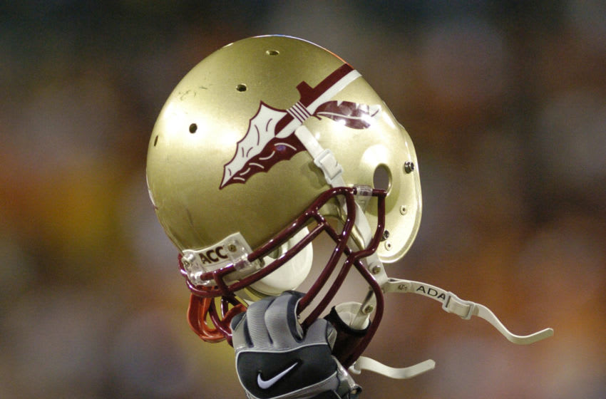Florida State players hoist helmets December 3 at the 2005 ACC Football Championship Game in Jacksonville. Florida State upset Virginia Tech to win an invitation to the BCC Orange Bowl game. (Photo by A. Messerschmidt/Getty Images) *** Local Caption ***