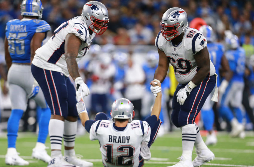 DETROIT, MI - SEPTEMBER 23: Trent Brown #77 of the New England Patriotsat and Shaq Mason #69 help their quarterback Tom Brady #12 of the New England Patriots up off the field after a sack during the second half at Ford Field on September 23, 2018 in Detroit, Michigan. (Photo by Rey Del Rio/Getty Images)