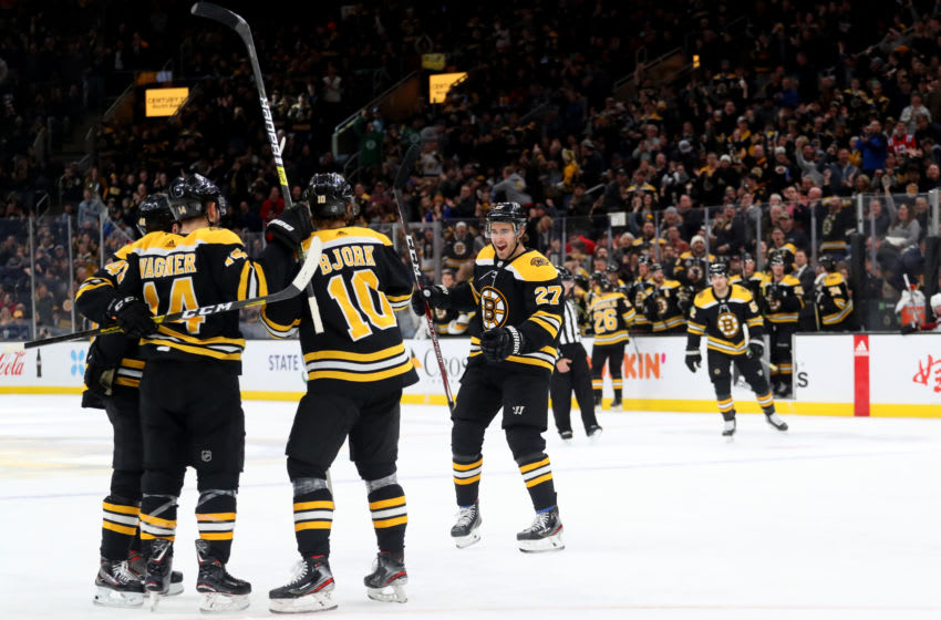 BOSTON, MASSACHUSETTS - DECEMBER 07: Anders Bjork #10 and John Moore #27 celebrate with Chris Wagner #14 of the Boston Bruins safter he scored a goal against the Colorado Avalanche during the first period at TD Garden on December 07, 2019 in Boston, Massachusetts. (Photo by Maddie Meyer/Getty Images)