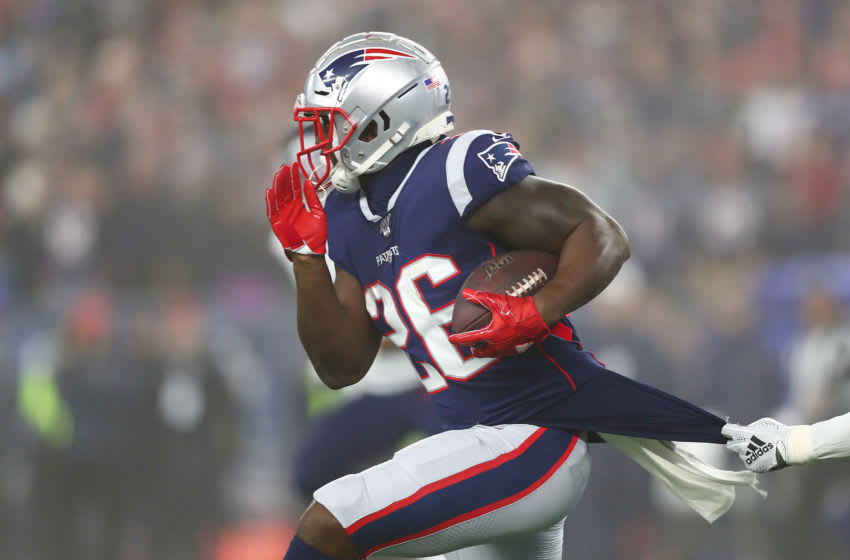 FOXBOROUGH, MASSACHUSETTS - JANUARY 04: Sony Michel #26 of the New England Patriots carries the ball against the Tennessee Titans in the first half of the AFC Wild Card Playoff game at Gillette Stadium on January 04, 2020 in Foxborough, Massachusetts. (Photo by Adam Glanzman/Getty Images)