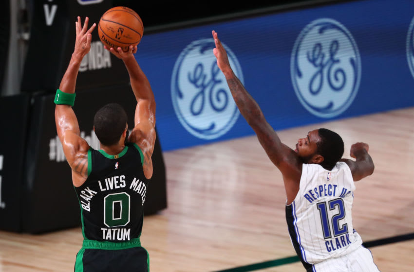 LAKE BUENA VISTA, FLORIDA - AUGUST 09: Jayson Tatum #0 of the Boston Celtics makes a three pointer over Gary Clark #12 of the Orlando Magic in the fourth quarter of a NBA basketball game at AdventHealth Arena at the ESPN Wide World Of Sports Complex on August 9, 2020 in Lake Buena Vista, Florida. NOTE TO USER: User expressly acknowledges and agrees that, by downloading and or using this photograph, User is consenting to the terms and conditions of the Getty Images License Agreement. (Photo by Kim Klement-Pool/Getty Images)