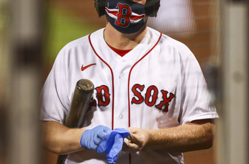 BOSTON, MA - JULY 28: The ball boy wears a protective face mask as he puts on medical latex gloves during the sixth inning of a game between the Boston Red Sox and the New York Mets at Fenway Park on July 28, 2020 in Boston, Massachusetts. (Photo by Adam Glanzman/Getty Images)
