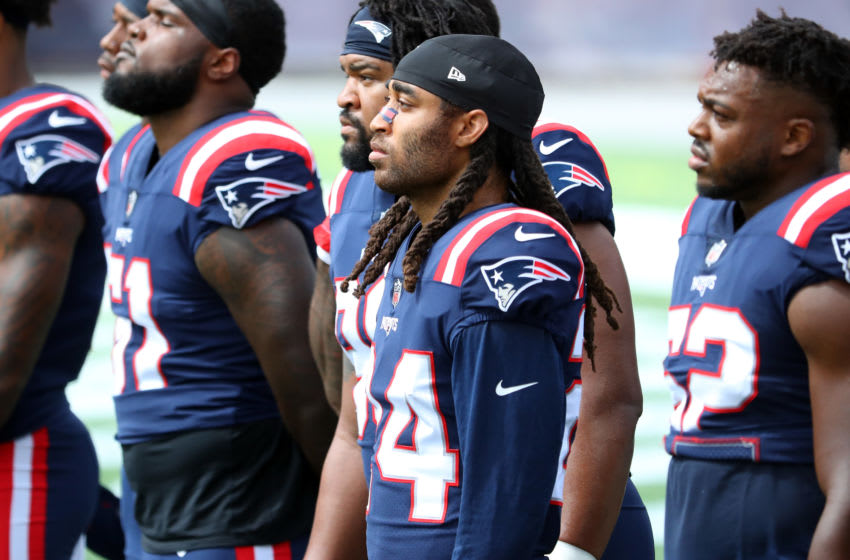 FOXBOROUGH, MASSACHUSETTS - SEPTEMBER 13: Stephon Gilmore #24 of the New England Patriots stands with teammates as Alicia Keys performs