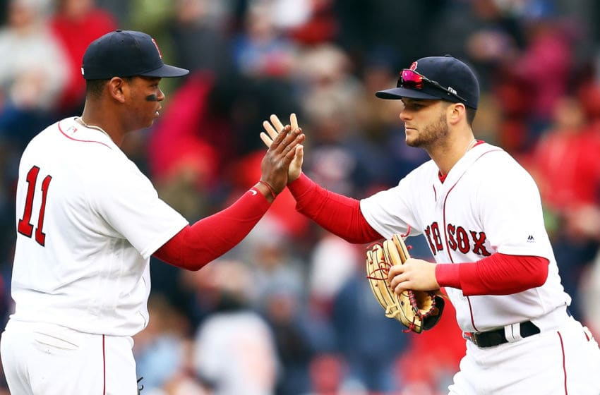 BOSTON, MA - APRIL 14: Rafael Devers #11 high fives Andrew Benintendi #16 of the Boston Red Sox after a victory over the Baltimore Orioles at Fenway Park on April 14, 2018 in Boston, Massachusetts. (Photo by Adam Glanzman/Getty Images)