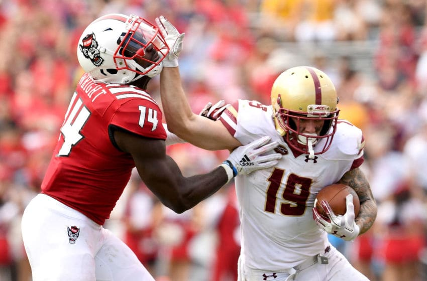 RALEIGH, NC - OCTOBER 06: Ben Glines #19 of the Boston College Eagles stiff-arms Dexter Wright #14 of the North Carolina State Wolfpack during their game at Carter-Finley Stadium on October 6, 2018 in Raleigh, North Carolina. North Carolina State won 28-23. (Photo by Grant Halverson/Getty Images)