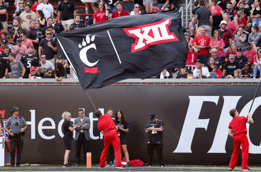 CINCINNATI, OHIO - SEPTEMBER 11: A Cincinnati Bearcats cheerleader waves a flag with the Cincinnati Bearcats and Big 12 logos during the game against the Murray State Racers at Nippert Stadium on September 11, 2021 in Cincinnati, Ohio. (Photo by Dylan Buell/Getty Images)