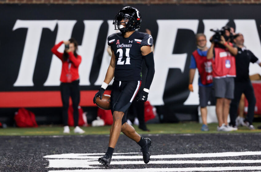 CINCINNATI, OHIO - OCTOBER 08: Tyler Scott #21 of the Cincinnati Bearcats celebrates after scoring a touchdown in the third quarter against the Temple Owls at Nippert Stadium on October 08, 2021 in Cincinnati, Ohio. (Photo by Dylan Buell/Getty Images)