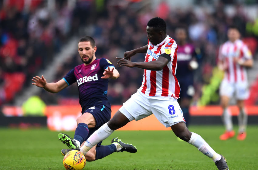 STOKE ON TRENT, ENGLAND - FEBRUARY 23: Mame Biram Diouf of Stoke City is tackled by Conor Hourihane of Aston Villa during the Sky Bet Championship match between Stoke City and Aston Villa at Bet365 Stadium on February 23, 2019 in Stoke on Trent, England. (Photo by Nathan Stirk/Getty Images)