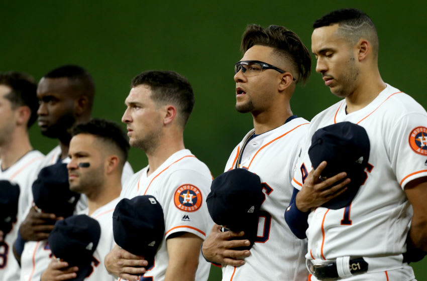 HOUSTON, TEXAS - OCTOBER 05: (L-R) Alex Bregman #2, Yuli Gurriel #10 and Carlos Correa #1 of the Houston Astros stand on the field during the national anthem before Game 2 of the ALDS against the Tampa Bay Rays at Minute Maid Park on October 05, 2019 in Houston, Texas. (Photo by Bob Levey/Getty Images)