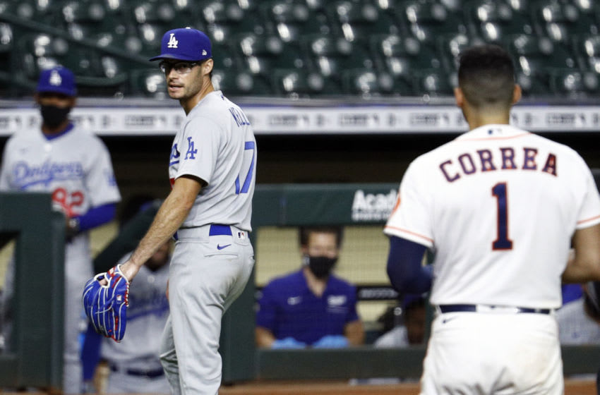 HOUSTON, TEXAS - JULY 28: Joe Kelly #17 of the Los Angeles Dodgers has words with Carlos Correa #1 of the Houston Astros as he walks towards the dugout at Minute Maid Park on July 28, 2020 in Houston, Texas. Both benches would empty after Kelly had thrown high inside pitches at Correa, Bregman and Guriel in the sixth inning. (Photo by Bob Levey/Getty Images)