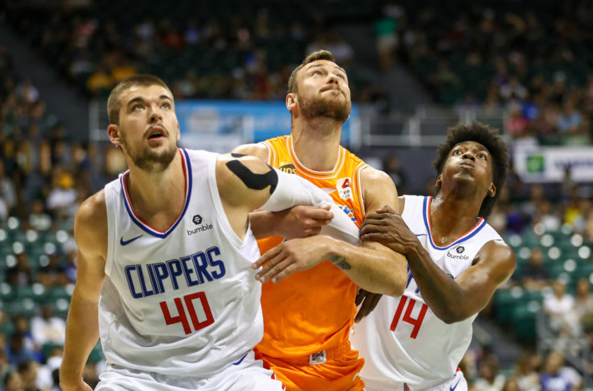 HONOLULU, HI - OCTOBER 06: Ivica Zubac #40 and Terance Mann #14 of the Los Angeles Clippers fight for position during a free throw attempt with Donatas Motiejunas #12 of the Shanghai Sharks at the Stan Sheriff Center on October 6, 2019 in Honolulu, Hawaii. TO USER: User expressly acknowledges and agrees that, by downloading and/or using this photograph, user is consenting to the terms and conditions of the Getty Images License Agreement. (Photo by Darryl Oumi/Getty Images)