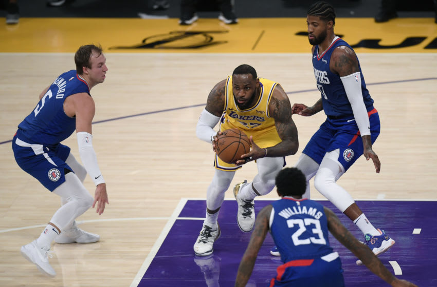 LOS ANGELES, CALIFORNIA - DECEMBER 22: LeBron James #23 of the Los Angeles Lakers looks to make a pass between Luke Kennard #5, Paul George #13 and Lou Williams #23 of the LA Clippers during a 116-109 Clippers win in the season opening game at Staples Center on December 22, 2020 in Los Angeles, California. NOTE TO USER: User expressly acknowledges and agrees that, by downloading and or using this photograph, User is consenting to the terms and conditions of the Getty Images License Agreement. (Photo by Harry How/Getty Images)