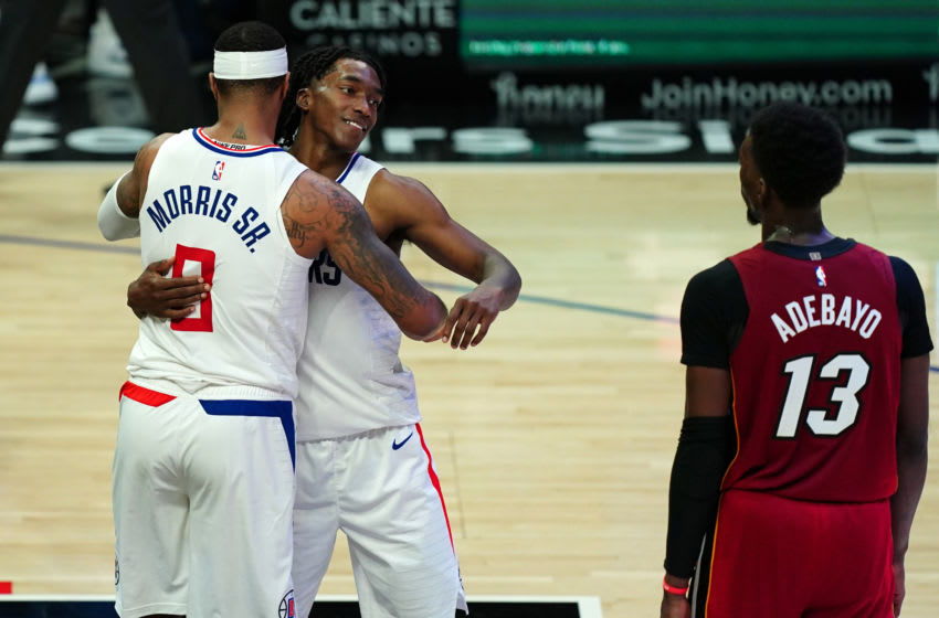 Feb 15, 2021; Los Angeles, California, USA; LA Clippers forward Marcus Morris Sr. (8) and guard Terance Mann (14) embrace at the end of the game as Miami Heat center Bam Adebayo (13) watches at Staples Center. The Clippers defeated the Heat 125-118. Mandatory Credit: Kirby Lee-USA TODAY Sports
