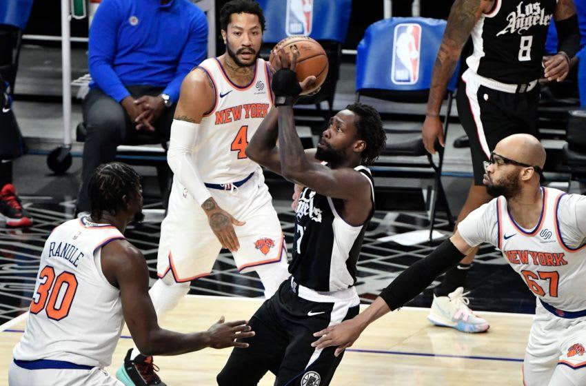 May 9, 2021; Los Angeles, California, USA; LA Clippers guard Patrick Beverley (21) drives to the basket between New York Knicks forward Julius Randle (30), guard Derrick Rose (4) and center Taj Gibson (67) during the first quarter. Mandatory Credit: Robert Hanashiro-USA TODAY Sports