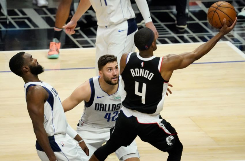 May 22, 2021; Los Angeles, California, USA; LA Clippers guard Rajon Rondo (4) drives to the basket past Dallas Mavericks forward Tim Hardaway Jr. (left) and forward Maxi Kleber (42) during the fourth quarter of game one in the first round of the 2021 NBA Playoffs at Staples Center. Mandatory Credit: Robert Hanashiro-USA TODAY Sports