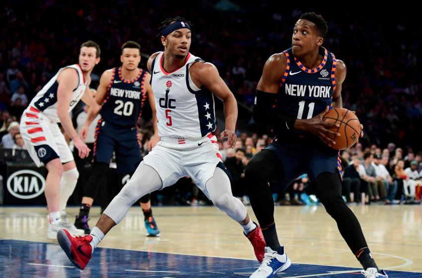 NEW YORK, NEW YORK - DECEMBER 23: Frank Ntilikina #11 of the New York Knicks drives past Justin Robinson #5 of the Washington Wizards during the second half of their game at Madison Square Garden on December 23, 2019 in New York City. NOTE TO USER: User expressly acknowledges and agrees that, by downloading and or using this photograph, User is consenting to the terms and conditions of the Getty Images License Agreement. (Photo by Emilee Chinn/Getty Images)