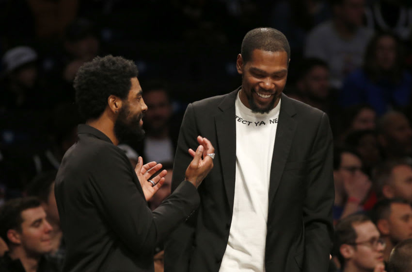 NEW YORK, NEW YORK - DECEMBER 26: (NEW YORK DAILIES OUT) Kyrie Irving (L) and Kevin Durant of the Brooklyn Nets have a laugh during a game against the New York Knicks at Barclays Center on December 26, 2019 in New York City. The Knicks defeated the Nets 94-82. NOTE TO USER: User expressly acknowledges and agrees that, by downloading and or using this photograph, User is consenting to the terms and conditions of the Getty Images License Agreement. (Photo by Jim McIsaac/Getty Images)