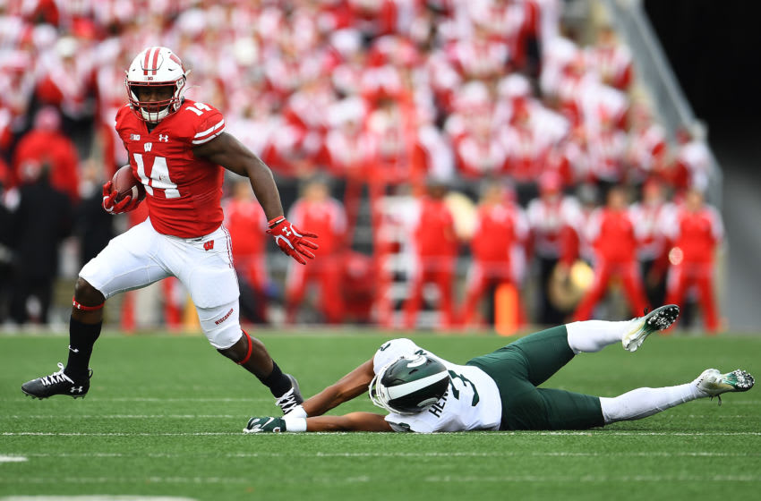 MADISON, WISCONSIN - OCTOBER 12: Nakia Watson #14 of the Wisconsin Badgers avoids a tackle by Xavier Henderson #3 of the Michigan State Spartans during the first half at Camp Randall Stadium on October 12, 2019 in Madison, Wisconsin. (Photo by Stacy Revere/Getty Images)