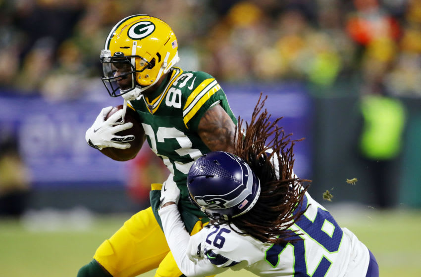 GREEN BAY, WISCONSIN - JANUARY 12: Shaquill Griffin #26 of the Seattle Seahawks attempts to tackle Marquez Valdes-Scantling #83 of the Green Bay Packers during the first half in the NFC Divisional Playoff game at Lambeau Field on January 12, 2020 in Green Bay, Wisconsin. (Photo by Gregory Shamus/Getty Images)