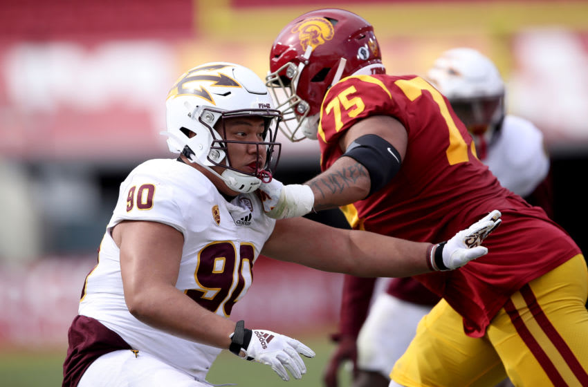 LOS ANGELES, CALIFORNIA - NOVEMBER 07: Jermayne Lole #90 of the Arizona State Sun Devils pushes off Alijah Vera-Tucker #75 of the USC Trojans during the second half of a game at Los Angeles Coliseum on November 07, 2020 in Los Angeles, California. (Photo by Sean M. Haffey/Getty Images)
