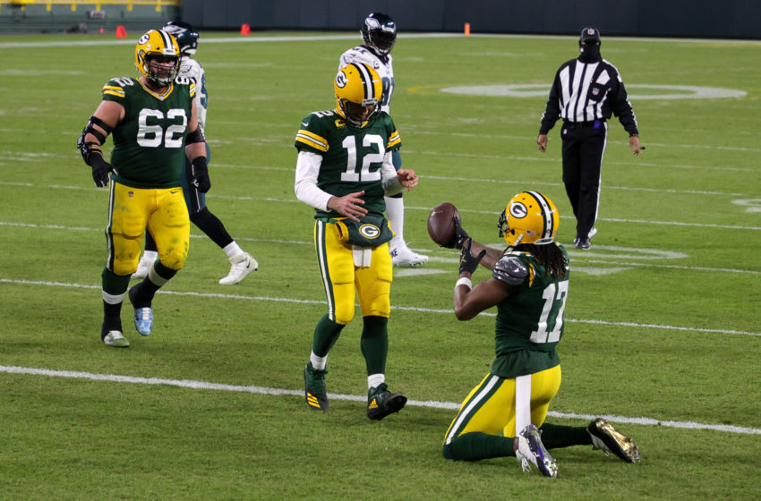 GREEN BAY, WISCONSIN - DECEMBER 06: Davante Adams #17 of the Green Bay Packers celebrates with teammate Aaron Rodgers #12 following a nine yard touchdown reception during the third quarter of their game against the Philadelphia Eagles at Lambeau Field on December 06, 2020 in Green Bay, Wisconsin. The touchdown marks Rodgers' 400th career touchdown pass. (Photo by Stacy Revere/Getty Images)