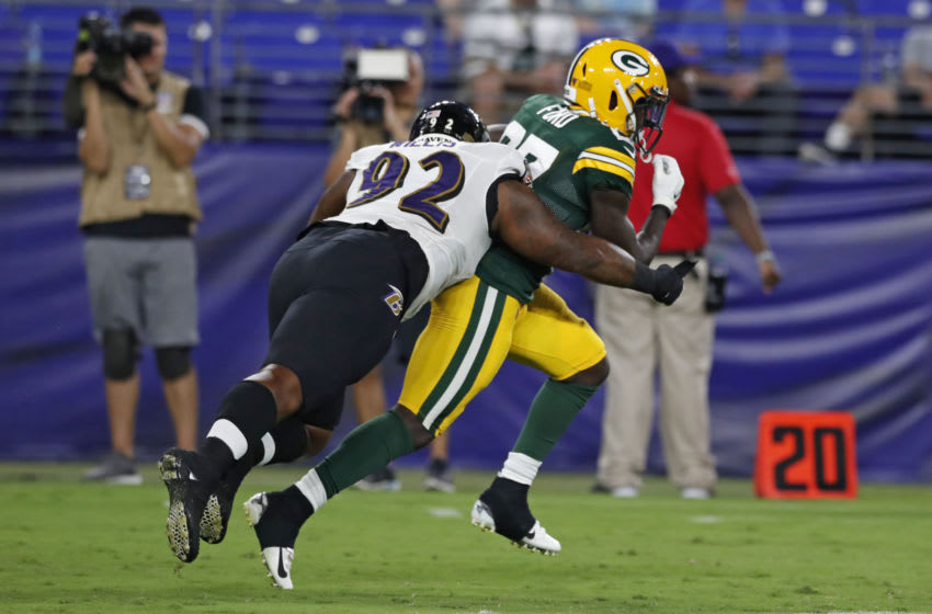 BALTIMORE, MARYLAND - AUGUST 15: Keith Ford #27 of the Green Bay Packers is tackled by Gerald Willis #92 of the Baltimore Ravens in the second half of a preseason game at M&T Bank Stadium on August 15, 2019 in Baltimore, Maryland. (Photo by Todd Olszewski/Getty Images)