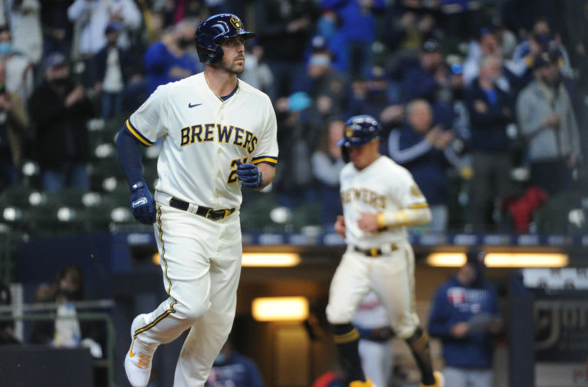 Apr 1, 2021; Milwaukee, Wisconsin, USA; Milwaukee Brewers third baseman Travis Shaw (21) walks in a base runner second baseman Kolten Wong (16) in the third inning against the Minnesota Twins at American Family Field. Mandatory Credit: Michael McLoone-USA TODAY Sports