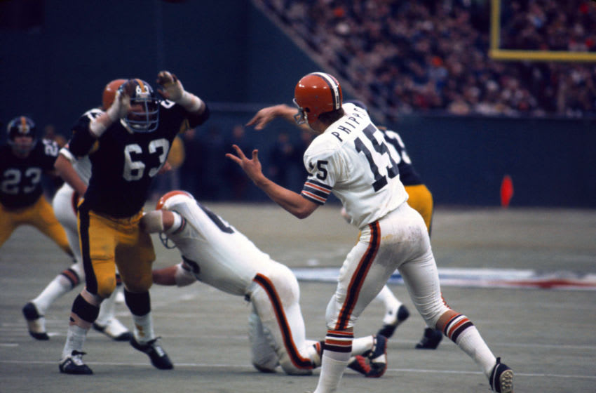 PITTSBURGH, PA - DECEMBER 03: Mike Phipps, quarterback for the Cleveland Browns, throwing a forward pass during an NFL football game between the Pittsburgh Steelers and the Cleveland Browns at Three Rivers Stadium on December 3, 1972. The Steelers' Defensive Tackle, Ernie Holmes, defends against pass. The Steelers beat the Browns, 30-0. (Photo By Ross Lewis/Getty Images)