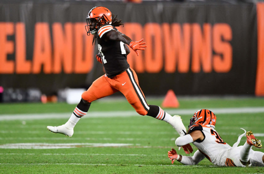CLEVELAND, OH - SEPTEMBER 17: Kareem Hunt #27 of the Cleveland Browns leaps out of the grasp of Jessie Bates III #30 of the Cincinnati Bengals in the fourth quarter at FirstEnergy Stadium on September 17, 2020 in Cleveland, Ohio. Cleveland defeated Cincinnati 35-30. (Photo by Jamie Sabau/Getty Images)