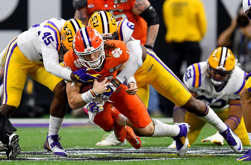 NEW ORLEANS, LOUISIANA - JANUARY 13: Trevor Lawrence #16 of the Clemson Tigers is tackled by Jacob Phillips #6, and Michael Divinity Jr. #45 of the LSU Tigers after a 9-yard run during the second quarter of the College Football Playoff National Championship game at the Mercedes Benz Superdome on January 13, 2020 in New Orleans, Louisiana. The LSU Tigers topped the Clemson Tigers, 42-25. (Photo by Alika Jenner/Getty Images)