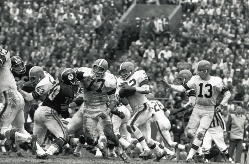 CIRCA 1960S: Dick Schafrath #77 of the Cleveland Browns blocks for Jim Brown #32 as Frank Ryan #13 looks on during a circa 1960s game against the Pittsburgh Steelers. (Photo by Robert Riger/Getty Images)
