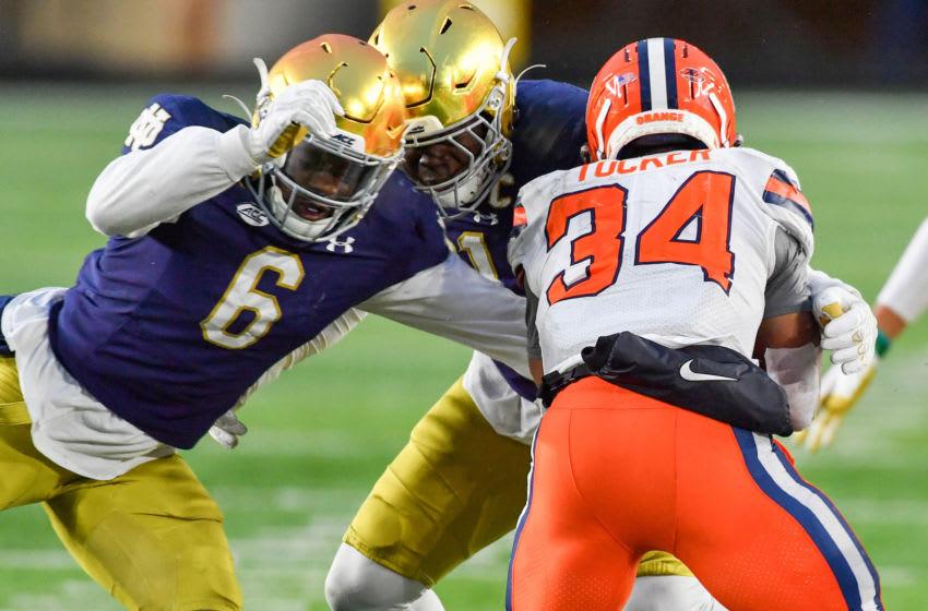 Dec 5, 2020; South Bend, Indiana, USA; Syracuse Orange running back Sean Tucker (34) is tackled by Notre Dame Fighting Irish linebacker Jeremiah Owusu-Koramoah (6) in the third quarter at Notre Dame Stadium. Mandatory Credit: Matt Cashore-USA TODAY Sports